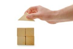 La mano stabilisce un tetto del giocattolo sui cubi di legno Immagini Stock