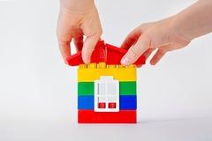 La mano stabilisce un tetto del giocattolo sui cubi di plastica passi mettere un tetto per comporre una casa su fondo bianco Cost Immagini Stock