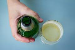 La mano su una bottiglia di birra verde e su una metà ha riempito il vetro Immagini Stock