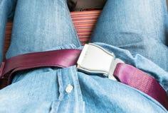 La mano sujeta el cinturón de seguridad en el asiento en el aeroplano antes saca Fotografía de archivo libre de regalías