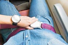 La mano sujeta el cinturón de seguridad en el asiento en el aeroplano antes saca Imagen de archivo