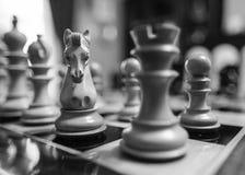 La mano talló, los pedazos de ajedrez de madera considerados en un tablero de ajedrez de la herida de la competencia fotos de archivo libres de regalías