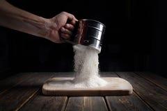 La mano tamiza la harina a través de un tamiz Imagen de archivo libre de regalías