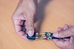 La mano tapa el cable de RCA a 3 enchufe estéreo audio de 5 milímetros fotos de archivo