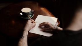 La mano tatuada del hombre escribe en un cuaderno en una mesa de centro en un primer del caf? metrajes