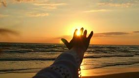 La mano tesa del ` s della ragazza è primo piano, toccante la luce solare, contro lo sfondo del declino del mare ad un lento archivi video