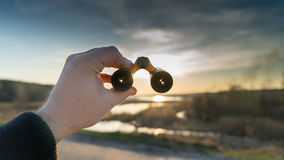La mano tiene il binocolo sul tramonto Fotografie Stock