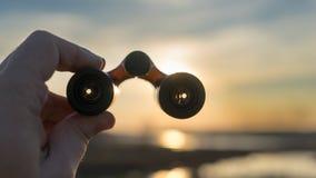 La mano tiene il binocolo sul tramonto Fotografia Stock