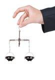 La mano tiene il metallo pesare le scale equilibrate Fotografie Stock Libere da Diritti