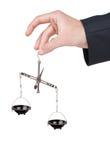 La mano tiene il metallo pesare le scale squilibrate Immagini Stock