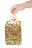 La mano tiene il pacchetto con i regali Immagini Stock