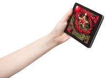 La mano tiene il pc della compressa con la stella ed il lamé rossi Immagine Stock Libera da Diritti