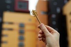La mano tiene le chiavi contro lo sfondo di nuove costruzioni Immagine Stock