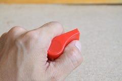 La mano tiene un fischio rosso Fotografia Stock