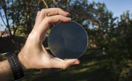 La mano tiene una lente su un fondo degli alberi fotografie stock