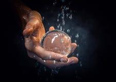 La mano tiene una sfera di vetro Fotografia Stock Libera da Diritti