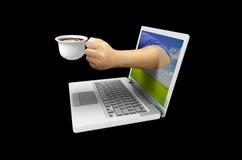 La mano tiene una tazza di caffè dallo schermo Fotografia Stock