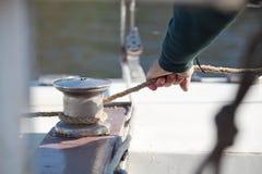 La mano tira de la cuerda alrededor del torno del primer del velero Imagenes de archivo