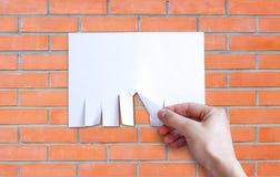 La mano tira pezzo di carta Isolato di carta vuoto degli a fogli mobili dell'annuncio Fotografie Stock