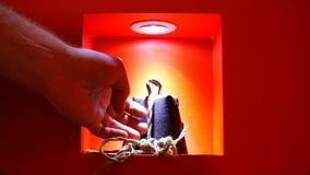 La mano toca el objeto expuesto de la exposición de una aleación rara bajo luz en un fondo rojo metrajes