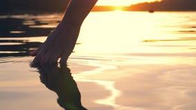 La mano toca suavemente la superficie del agua en la puesta del sol de oro almacen de video