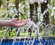 La mano tocca l'acqua dolce pulita e Immagine Stock
