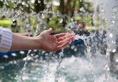 La mano tocca l'acqua dolce pulita e Fotografia Stock Libera da Diritti