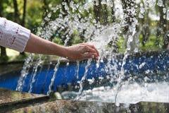 La mano tocca l'acqua dolce pulita e Fotografia Stock
