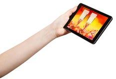 La mano todavía sostiene la tableta-PC con vida de Navidad Imágenes de archivo libres de regalías