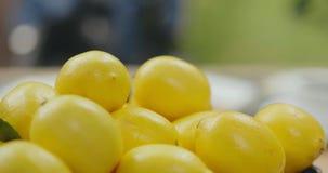 La mano toma el limón amarillo fresco en la tienda de la fruta almacen de metraje de vídeo