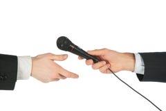 La mano toma el micrófono de otro Imagen de archivo libre de regalías