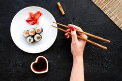 La mano toma el rollo de sushi con los salmones y el aguacate con el palillo Opinión superior del fondo negro Fotografía de archivo