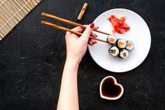 La mano toma el rollo de sushi con los salmones y el aguacate con el palillo Opinión superior del fondo negro Fotos de archivo libres de regalías