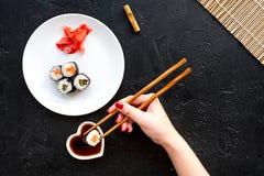 La mano toma el rollo de sushi con los salmones y el aguacate con el palillo Opinión superior del fondo negro Foto de archivo libre de regalías