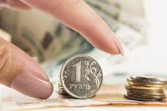 La mano toma la rublo y los dólares con los bancos de rublos Imagen de archivo