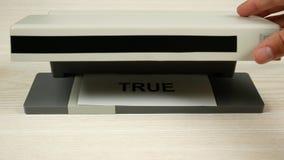 La mano trae al detector al trozo de papel con la inscripción verdad Cambia a falso almacen de video