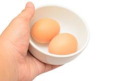 La mano trae los huevos en una taza aislada en el fondo blanco Imágenes de archivo libres de regalías