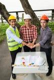 La mano tres de ingenieros toma la coordinación y mira a la cámara para hace un acuerdo en la inversión sobre la construcción imagen de archivo