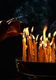 La mano umana accende una candela nella chiesa Fotografie Stock