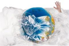 La mano umana esce dalla plastica vicino al globo, lavandini umani nella plastica, il nostro consumo irresponsabile e eccessivo d Fotografie Stock