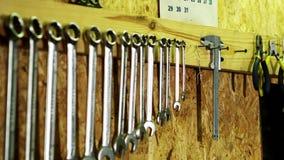 La mano umana prende il calibro a corsoio dalla parete Insieme degli strumenti meccanici in garage stock footage