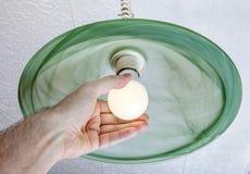 La mano umana torce la lampada del LED nel vetro verde del dispositivo del soffitto Immagine Stock Libera da Diritti