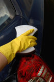 La mano in un guanto giallo lava l'automobile fotografie stock libere da diritti