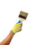 La mano in un guanto sta giudicando una spazzola isolata su fondo bianco Fotografie Stock