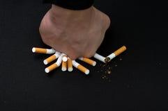 La mano un puño rompe los cigarrillos Imagen de archivo libre de regalías