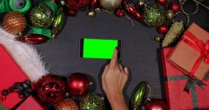La mano utilizza lo smartphone fra la decorazione di Natale video d archivio