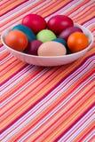 La mano variopinta ha tinto le uova di Pasqua in una ciotola su una tavola con a strisce Fotografia Stock Libera da Diritti