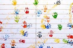 La mano variopinta timbra sulla parete di legno bianca per uso come fondo Fotografia Stock
