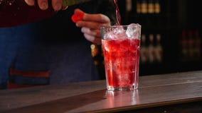 La mano versa il succo sopra i cubetti di ghiaccio in un vetro alla barra archivi video