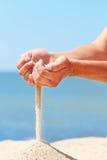 La mano versa la sabbia Immagini Stock